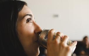 Chica tomando lata de cerveza