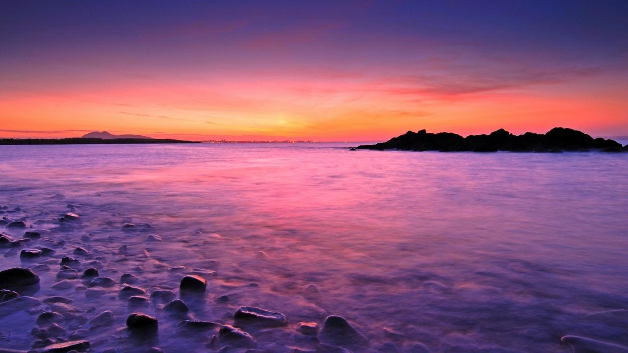 Amanecer en playa rocosa - 1280x720