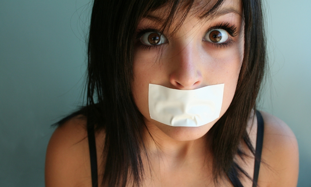 Chica con la boca tapada - 1000x600