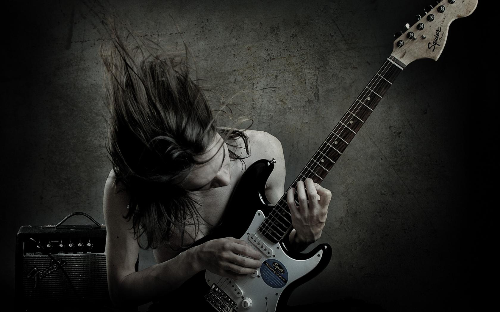 Un guitarrista con una Squier - 1680x1050