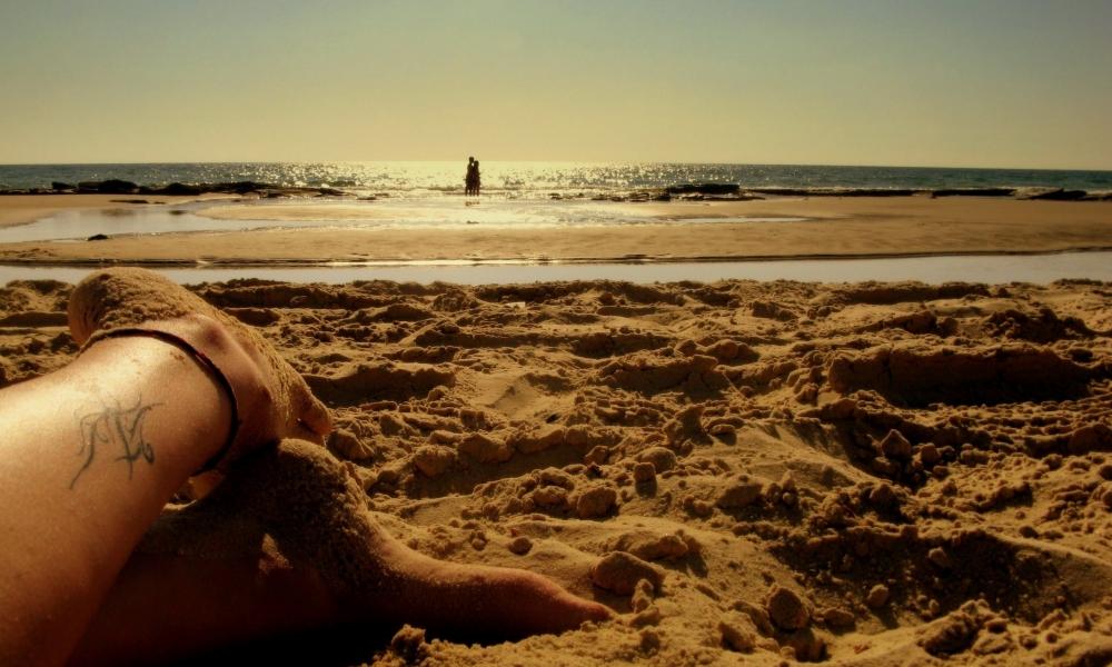 Los pies de una chica en la playa - 1000x600
