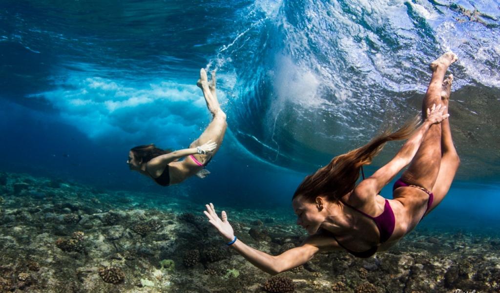 Chicas nadando bajo las olas - 1024x600