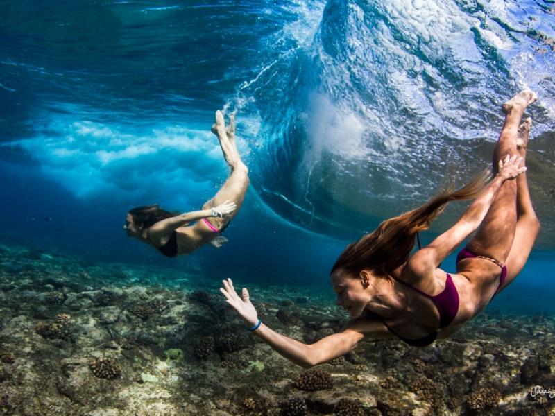 Chicas nadando bajo las olas - 800x600