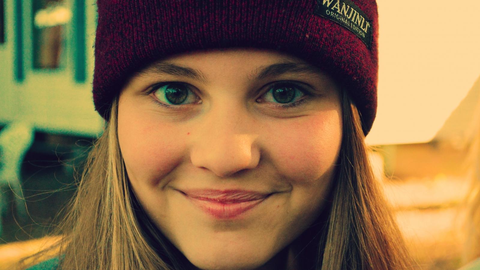 Chica sonriendo con gorra - 1600x900