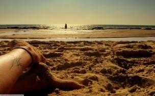Los pies de una chica en la playa