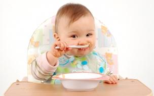 Un bebe comiendo su pure
