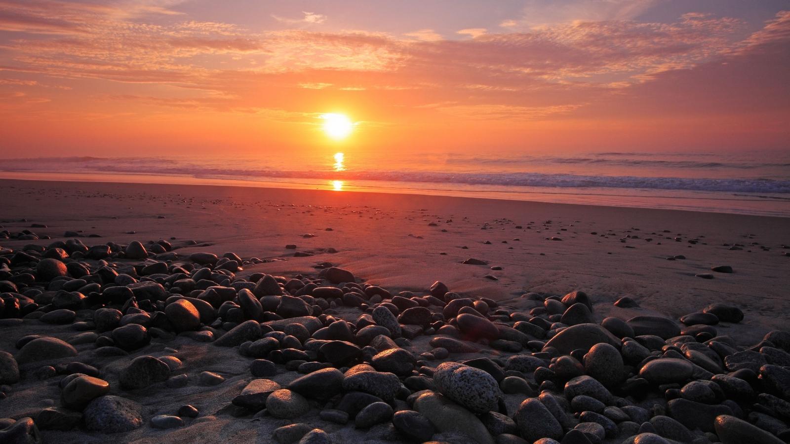 Rocas en una playa al atardecer - 1600x900