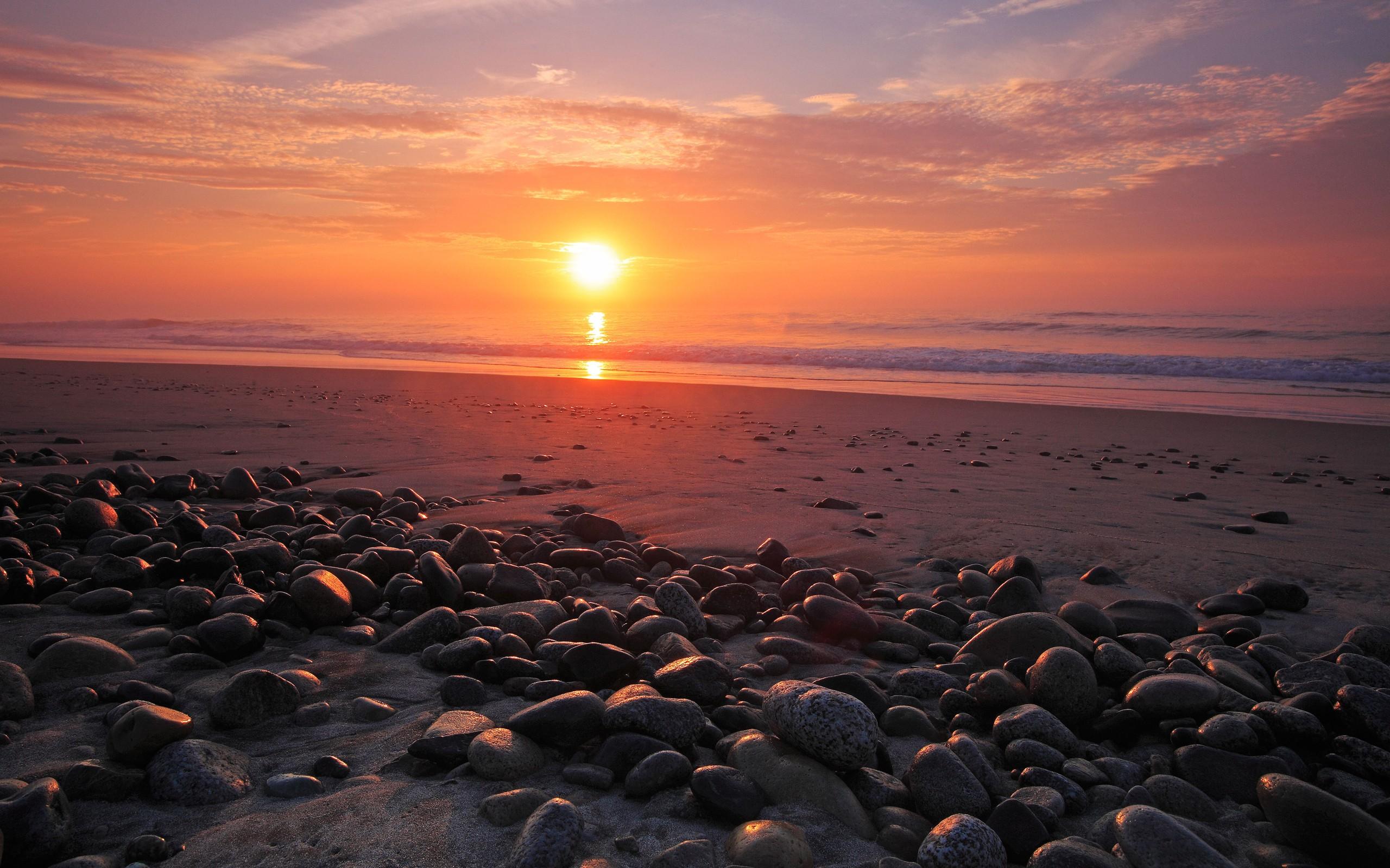 Rocas en una playa al atardecer - 2560x1600